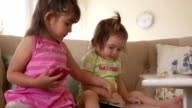 Older Sister Shows Younger One How to Use a Tablet Computer video