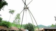 Sister swinging her  boy on a swing in mountain village video