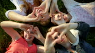 4 Sisters Lay In Grass, Hold Up Hands To Make Heart Shapes, They Smile video