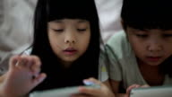 Sisters playing electronic games on smartphone video