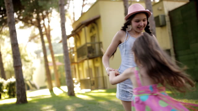 Sisters running around in garden and laughing video