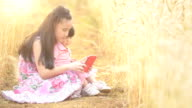 Sisters using tablet in the wheat field video