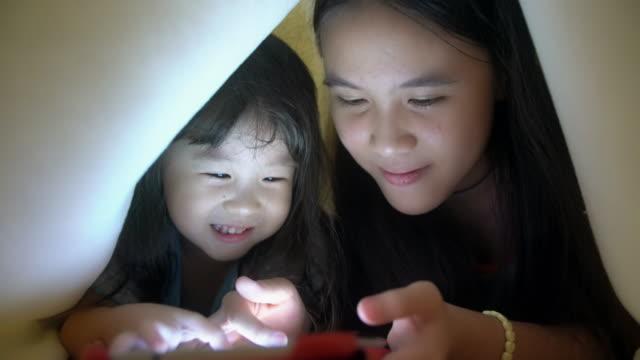 Sisters using tablet under the blanket video