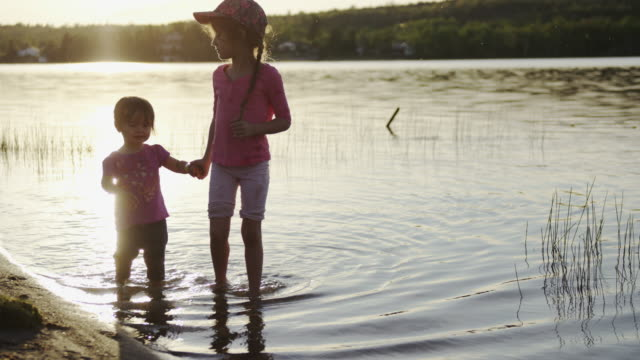 Sisters wading in the lake water at sunset video