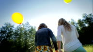 Sisters Walk Through Meadow, With Yellow Balloons video