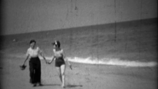 1936: Sisters walking together on beach in swimwear fashion and high pants. video