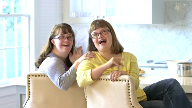 Sisters with down syndrome sitting in kitchen, talking video