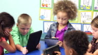 Six multi-ethnic children in schiool using digital tablets video