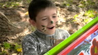 Six-year-old boy draws paints on whatman paper and smiling video