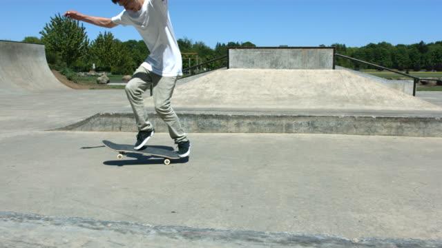Skateboarder does flip trick, slow motion video