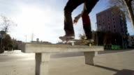 SLOW MOTION CLOSE UP: Skateboarder doing tricks jumping and sliding on the bench video