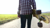 Skateboarder holding longboard and walking on the road video