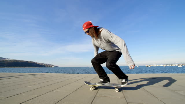 SLOW MOTION: Skateboarder jumping and doing a flip trick on concrete beach video