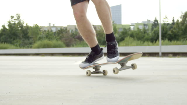 SLOW MOTION CLOSE UP: Skateboarder jumping and doing flip trick on city street video