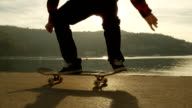 SLOW MOTION, CLOSE UP: Skateboarder jumping and turning skateboard in the air video
