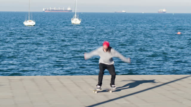 CLOSE UP: Skateboarder jumping doing 360 flip trick riding along the seashore video