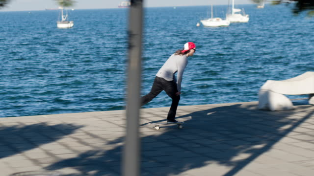 CLOSE UP: Skateboarder jumping doing kickflip trick riding along the coast video