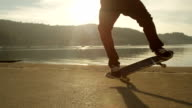 SLOW MOTION CLOSE UP: Skateboarder jumping doing tricks on the beach at sunset video