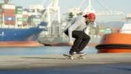 SLOW MOTION Skateboarder jumping performing heelflip trick on skateboard in port video