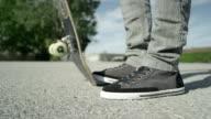 SLOW MOTION CLOSE UP: Skateboarder picks up his skate video