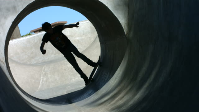 Skateboarder rides a full pipe, slow motion video