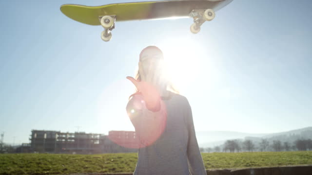 CLOSE UP: Skater flipping skate in the air pushing it into the camera over sun video