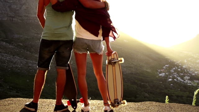 Skater friends looking at sunset video