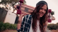 Skater girl standing with her board on her shoulders smiling video