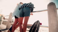Skater girls in shorts standing at the seaside with skateboards video