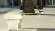 SLOW MOTION: Skater grinding with skate on concrete bench doing nose slide trick video