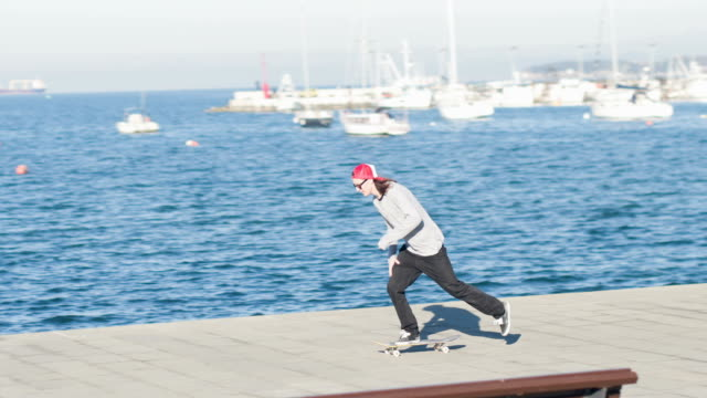 CLOSE UP: Skater jumping doing ollie and kickflip tricks riding along the coast video