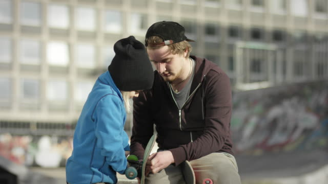 Skater reparing skateboard with his father video