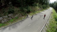 AERIAL: Skaters on longboard driving in slow motion through forest video