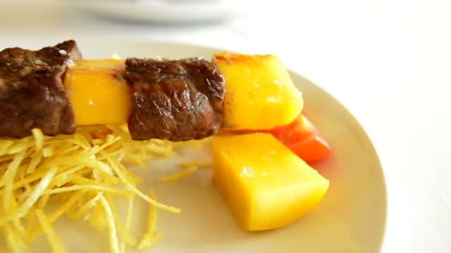 Skewer of mango fruit and meat of cow or beef at grill panoramic video