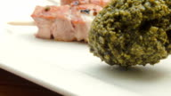Skewers of turkey on a white plate with pesto video
