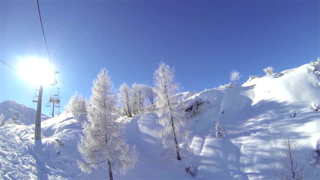 Ski lift ride on sunny day video