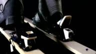 Skier attaching his ski boots, rear closing/opening of ski on black background, black and white video video