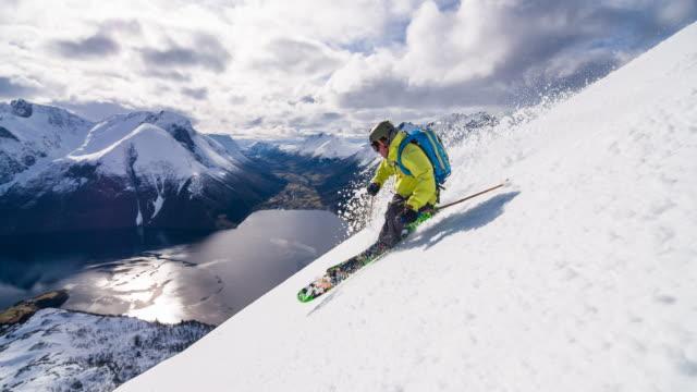 Skier doing powder turn above Norwegian fjord video