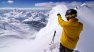 Skier on top of mountain ridge pointing at view video