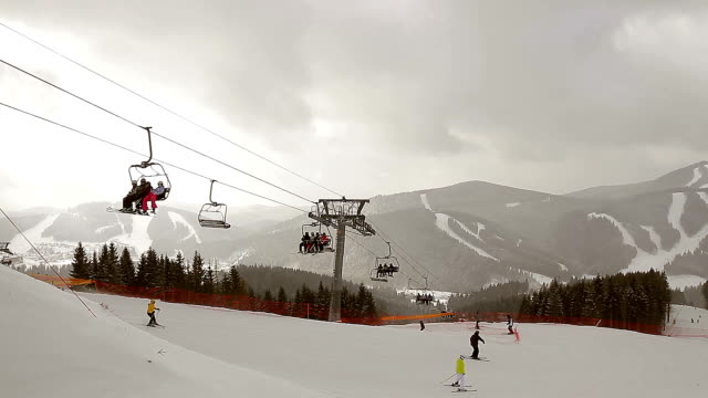 Skiers ascend on chairlift. video