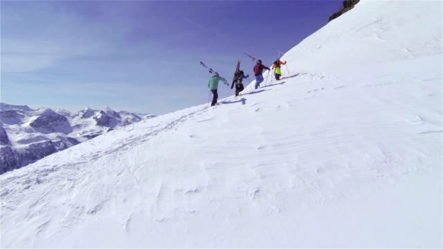 AERIAL: Skiers hiking uphill, carrying the skis video