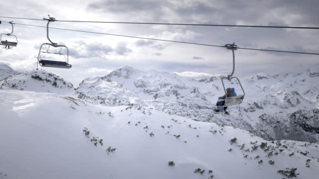 AERIAL Skiers riding a chairlift and enjoying wonderful winter scenery video