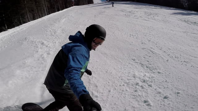 Skiing in the Alps in the winter. A man is rolling on a snowboard on the snow-covered trails of a mountain resort. The guy takes himself off on an extreme camera video