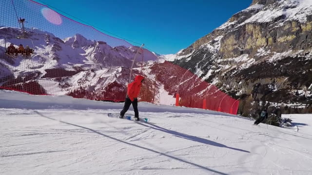 Skiing in the Alps in the winter. A man is rolling on a snowboard on the snow-covered trails of a mountain resort. Extreme skiing and active lifestyle, add adrenaline to the blood video