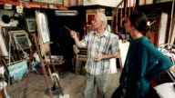 Skilled artists discussing a painting in studio video