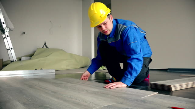 Skilled master builder laying wooden laminate boards on floor video