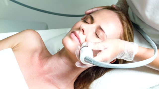 Skillful beautician treating female face by special equipment video