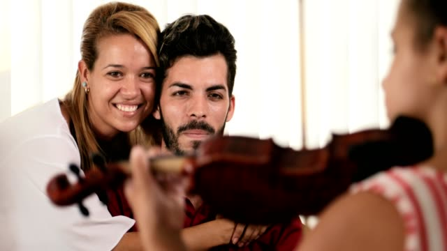 Skillful Daughter Playing Violin In Front Of Happy Mom Dad video