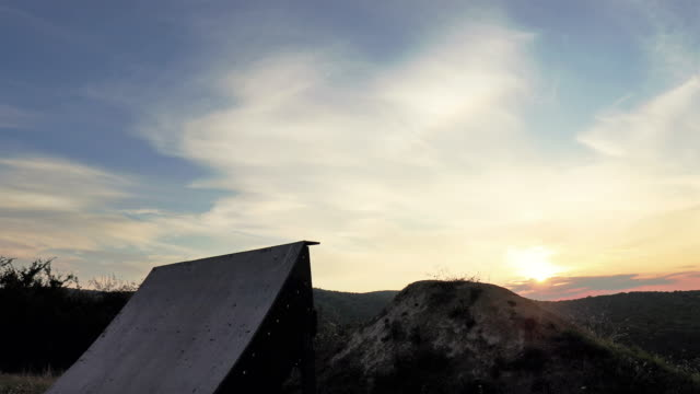 Skillful extreme cyclist jumping over sports ramp against the sky at sunset. video