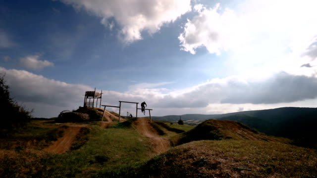 Skillful mountain bike cyclist jumping over dirt hills while exercising on extreme terrain. video